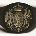 Écu ovale, couronne de comte surmontée d'une étoile, supports de griffons posés sur un décors (chevalière passée au noir de fumée)